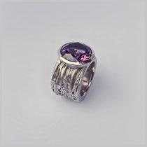 Ring in Silber. Die ungleichen Umschlingungen bilden einen Ring, der einen runden strahlenden Amethyst trägt.