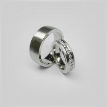 Gerade gearbeitete Ringe in Platin. Entlang der Mitte des kleineren Ringes läuft eine Linie aus gefassten Brillianten.