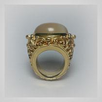 Ring in Gold, der erhöhte Aufbau hat eine ornamental durchbrochene Struktur. Mit hellbeige schimmernden Mondsteincabouchon.
