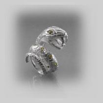 Opulenter Ring in Silber. Der gravierte, sich vergrößernde Schlangenkörper erhebt sich zum Kopf, ist fortlaufend mit Peridots besetzt.