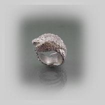 Ring in Silber mit zwei sich umschlingenden Körpern. Mit einer Rosen und Efeu nachempfundenen Struktur.