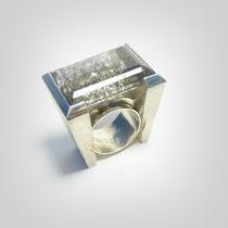 Geometrisch aufgebauter Ring in Silber mit leuchtendem rechteckigem Quarz mit Turmalinrutilen.