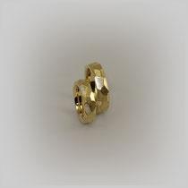 Ringe in Gelbgold. Die Oberfläche weist unterschiedlich große, eckige Flächen auf, deren Konturen durch Gravuren stark hervorgehoben sind.