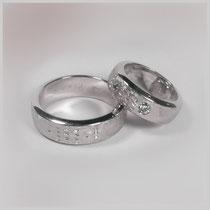 Ringe in Weißgold. In die mattierte Oberfläche sind individuelle Jahreszahlen eingraviert und, bei dem kleineren Ring, Diamanten eingesetzt.