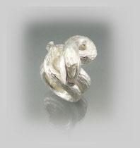 Schwerer Ring in Silber, das Äußere zeigt durch die Bearbeitung einen schuppenartigen Charakter.