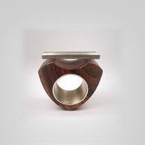 Grafisch gearbeiteter Ring aus Nussholz und Silber, der gefasste Aquamarinstab scheint fast über dem Ringtableau zu schweben.