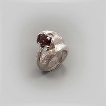 Ring in Silber in abstrahierter Form, das Schlangenmaul trägt einen rechteckigen, facettierten Rhodolith.