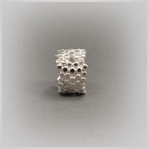 Bandring in Silber mit aneinander gehefteten, auf einer Ebene glänzenden Tropfen.