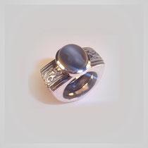 Dreiseitig aufgebauter Ring in Silber und Gold mit mittig laufendem Dekor. Schimmernder grauer Mondsteincabouchon.