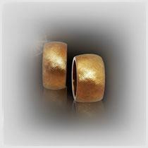 Schwere Ringe in Gold, die breite, leicht gewölbte Oberfläche zeigt eine starke Schraffur. Im Gegensatz dazu sind die Ringseiten glatt poliert.