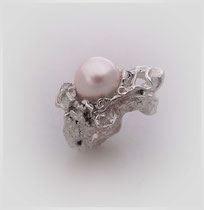Ring in Silber. Von der amorphen, sich aufstürzenden Form wird eine Perle gehalten.