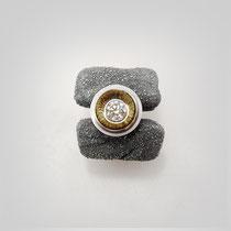 Schwerer, organisch geformter Ring in dunklem Silber, von einem herausgestellt gearbeiteten Diamanten gekrönt.