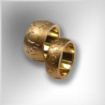 Ringe in Gold mit gewölbter, matter Oberfläche und gestochenen Ornamenten.