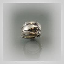 Ring in Silber, grafisch abstrahiert mit hell-dunklen Schattierungen.