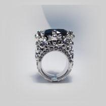 Ring in Weißgold. Geschlungene Ornamente erheben einen runden, facettierten Saphir. Mit schwarzen Diamanten.