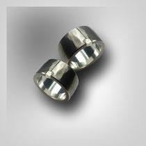 Gerade Ringe in Weißgold mit angedeutetem Hammerschlagmuster und seitwärts eingefasstem Rohdiamanten.