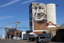 Ein Mural von Guido van Helten, aus Australien, gemalt auf Hauswand und Silo, im alten Hafenbereich, der jetzt modernisiert wird.