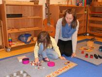 Elisabeth  beobachtet Klara bei der Arbeit mit Zahlenmaterial.