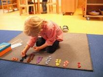 Marie legt Farbplättchen passend zu den Ziffern auf.