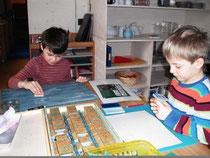 Die Schulanfänger Paul und Marcus stempeln Buchstaben und Wörter.