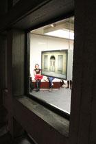 Blick von außen in den Galerieraum, im Fenster ein Leuchtkasten von Christine Kisorsy
