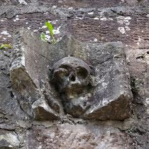 Stein mit Schädelrelief an der Außenmauer