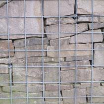 Gabione mit sorgfältig geschichteten Natursteinen.