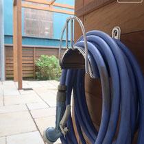 邪魔だった立水栓は壁面構造に埋設し、散水ホースは裏面に片付けるフックを用意しました。