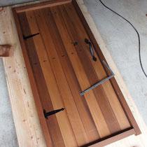 あらかじめ作業場で門扉を作成、素材はレッドシダーにダークブラウンの防腐剤を塗装して、アイアンの飾りを取付ます。