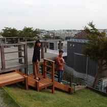 傾斜地に木製階段が完成、すっかりグレーに変色した既存のウッドデッキとも相性が良い仕上がりです。