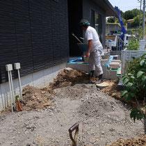工事着工。舗装をする場所には掘削と砕石を転圧、階段を兼ねる化粧平板舗装を、斜め切断加工しながら配置させていきます。
