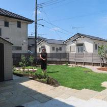 完成の記念撮影。お手入れのかかる芝生は最小限にして、周囲を石貼りやエッジ材で囲み、花壇を楽しめるようにしました。
