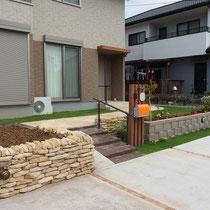 スロープ付のアプローチ階段を中心に、左側にはコッツウォルズの石積の家庭菜園があります。
