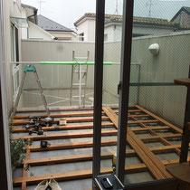 勾配のついた防水床面に、高さを調整する束柱で根太を設置します。