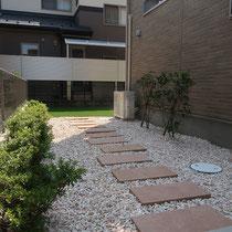 完成写真、雑草対策として、エントランス部分は平板と化粧砂利、中庭は人工芝で仕上げました。