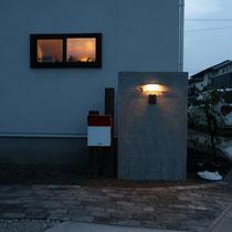 夜に灯る門灯、シンプルなモノトーンの玄関には彩りある植栽がとても映えそうです。