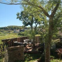 奥行き感を感じる石の門塀とウッドデッキ。大きなヤマモモの木を囲むように作成しました。