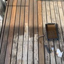 洗浄後に乾いた床面、こげ茶色の防腐塗料を染み込ませていきます。