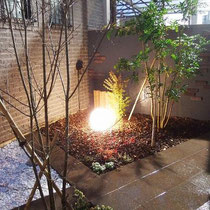 玄関脇を飾る坪庭の完成写真。夜にはぼんやりと灯る明かりで、落ち着いた印象を一層感じます。