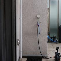 建物についた水栓と排水口、壁面にはスイッチの蓋と照明がついてます。