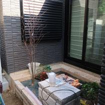 日陰にも耐えるエゴノキを植えこみ、石台の周りに雑草防止シートと低木を入れます。