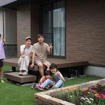 完成の記念撮影。家族でくつろぐ、花壇とデッキと人工芝があるお庭です。
