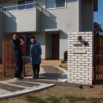 白いタイル張りの美しい家にあう、白レンガとすっきりした縦格子のウッドフェンス門塀。ご家族で記念撮影させて頂きました。