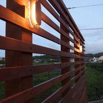 サマーキャンペンのライトを組み込んだフェンス。上下の隙間を変えて閉塞的にならないようにしました。