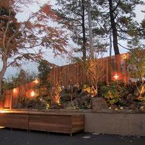 今まで3台の物置で隠れていた傾斜部分の敷地に、外周をウッドフェンス、景石と植栽で造園工事、ライトアップで映えるお庭をつくりました。