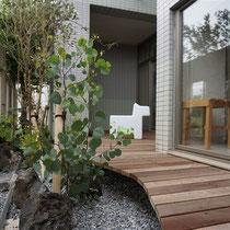 雑草防止シートで覆い砂利を敷きこんでからカーブ型のデッキを作成。植栽と照明を配置して可愛い屋外ファニチャーを置きました。