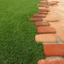 レンガ縁石はランダムテイストで設置したので、人工芝も凹凸をあわせ接着します。