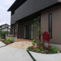 玄関に繋がるスロープの石畳とデッキ、駐車場が広いお庭とは切り離したデザインで使い勝手をすみわけします。