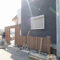 施工中の写真。木材のフェンスと石の土留めによる自然な風合いが馴染みます。