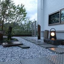 和室小窓前の風景、静かに灯る灯篭や六方石の石組に、モダンな平板飛石が融合します。